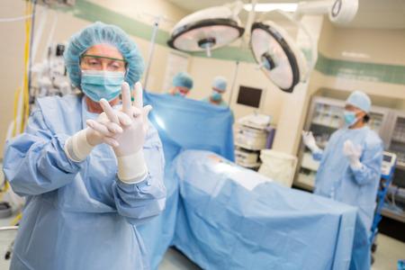 Mature female surgeon in operating suite adjusting latex gloves photo