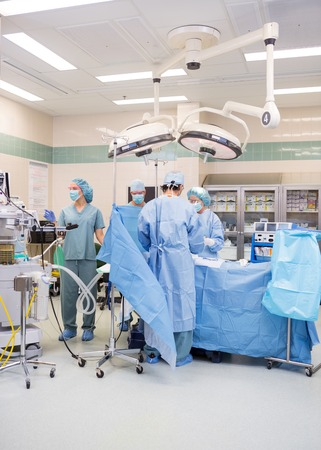 operation gown: Doctors operating patient in operation room