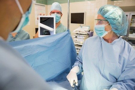 operation gown: Male nurse showing digital tablet to surgeons during surgery in operation room