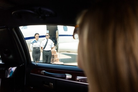 View of airhostess and pilot standing against private jet through limousine window photo