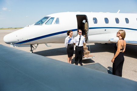 Elegant woman walking towards private jet while pilot and stewardess standing at airport terminal photo