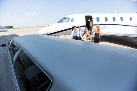 Woman boarding private jet with limousine in foreground at airport terminal photo
