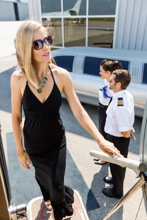 Full length of rich woman boarding private jet with pilot and airhostess standing by at airport terminal photo