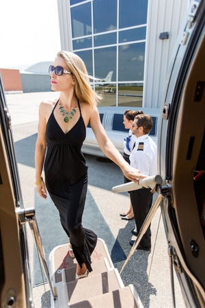 limo: Elegant woman in dress boarding private jet with pilot and airhostess standing by at airport terminal Stock Photo