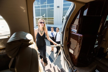 Beautiful woman in dress boarding private plane with pilot and airhostess standing by at airport terminal photo