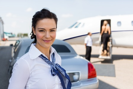 Portrait of beautiful airhostess standing against limousine and private jet at airport terminal photo