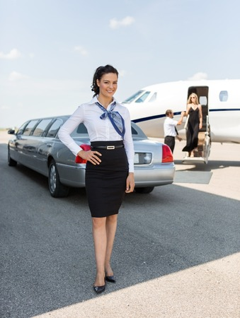 Full length portrait of attractive stewardess standing against limousine and private jet at airport terminal