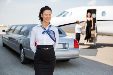 リムジンと空港ターミナルに私用ジェット機に対して立っている魅力的なスチュワーデスの肖像画 写真素材