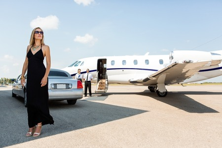 Full length of rich woman in elegant dress standing against limousine and private photo
