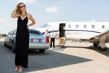 Full length of wealthy woman in elegant dress standing against limousine and private photo