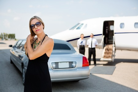 Elegant woman making hair while standing against limousine and private jet photo