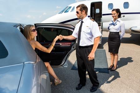空港ターミナルで車から歩むパイロット支援エレガントな女性の完全な長さ 写真素材