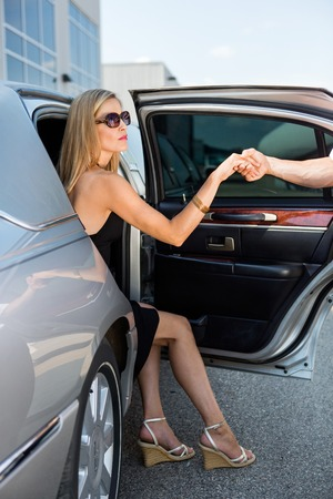 Mans hand helping elegant woman stepping out of car at airport terminal photo