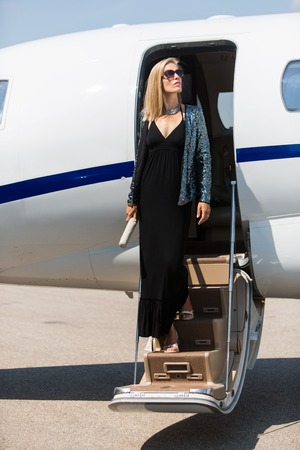 Wealthy woman in elegant dress stepping out of private jet photo