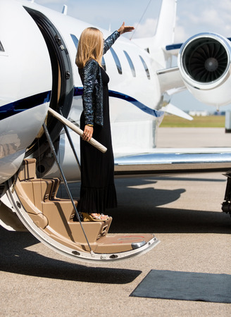 Full length of elegant woman stepping out of private jet photo