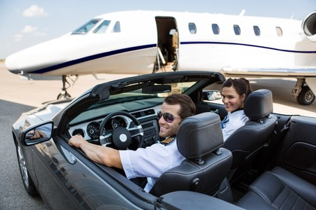 Happy pilot and airhostess in convertible against private jet at terminal photo