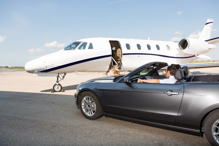 private jet: Pilot in convertible parked against private jet at airport terminal