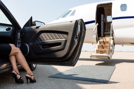 プライベート飛行機の前に停まっている車から歩む裕福な女性の低いセクション