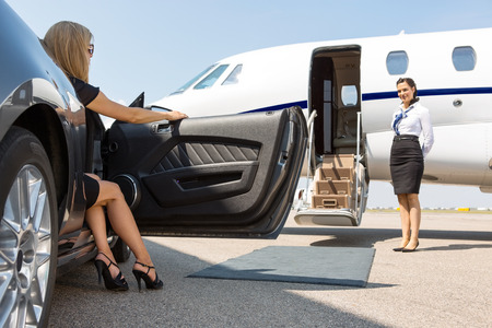 Elegant woman stepping out of car parked in front of private plane and airhostess Foto de archivo