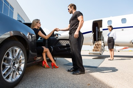 private jet: Full length of bodyguard helping elegant woman stepping out of car at airport terminal Stock Photo