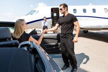 private security: Bodyguard helping elegant woman stepping out of car at airport terminal