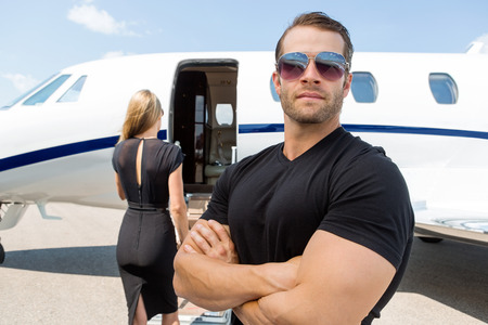 private security: Confident bodyguard wearing sunglasses while standing against woman and private jet Stock Photo