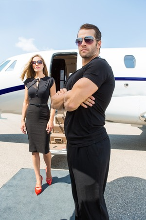 Bodyguard with arms crossed standing against elegant woman and private jet