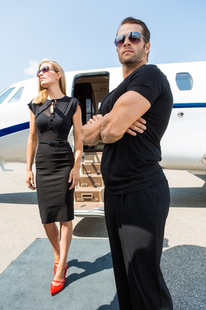 Elegant woman with bodyguard standing against private jet photo