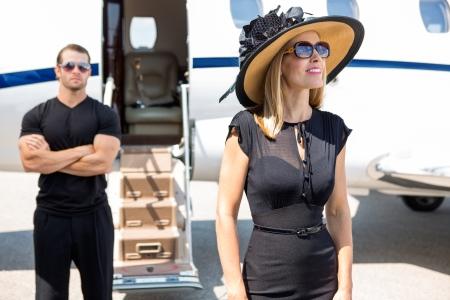 millonario: Feliz mujer con sombrero y gafas de sol con guardaespaldas y el jet privado en el fondo