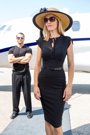 body guard: Beautiful woman in elegant dress with bodyguard and private jet in background