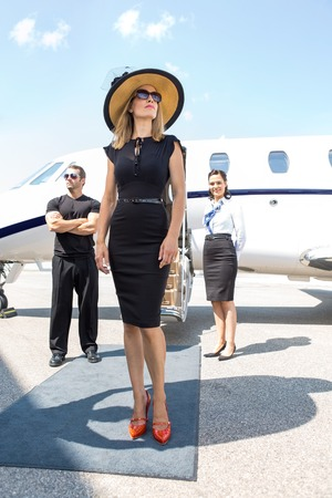 Beautiful woman in elegant dress with bodyguard and airhostess standing against private jet photo