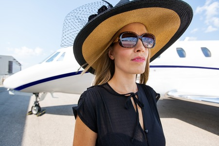Elegant woman wearing sunglasses and sunhat against private jet photo