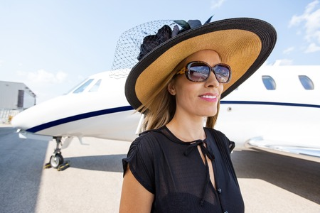 private: Beautiful rich woman standing against private jet Stock Photo