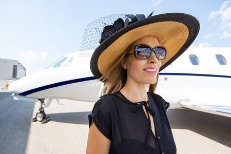 rijke vrouw: Mooie rijke vrouw die zich tegen prive-jet