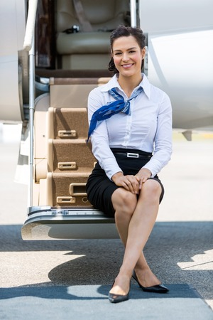flight crew: Full length portrait of beautiful stewardess sitting on ladder of private jet Stock Photo