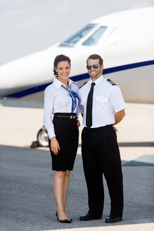 Full length portrait of confident airhostess and pilot standing against private jet at terminal photo