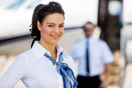ターミナルでバック グラウンドでパイロットとプライベート ジェットに笑みを浮かべて美しいスチュワーデスの肖像画 写真素材