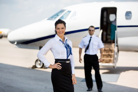 Portrait of confident stewardesses smiling with pilot and private jet in background at terminal Stock Photo