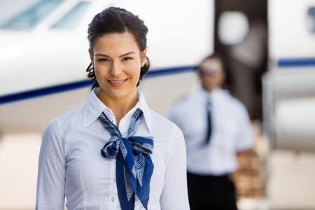 piloto: Retrato de hermosas azafatas sonrientes con el piloto y el jet privado en el fondo por la terminal del aeropuerto