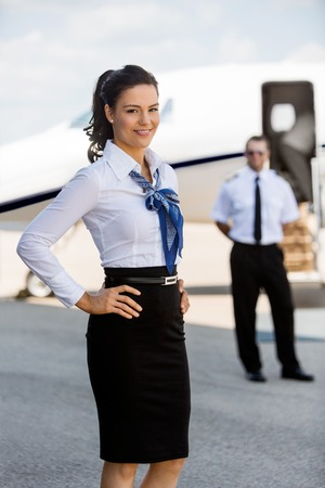 Portrait of confident airhostess with hands on hip smiling against pilot and private jet at airport terminal Stock Photo