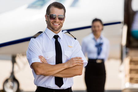 Portrait of confident pilot with arms crossed against stewardess and private jet at terminal photo