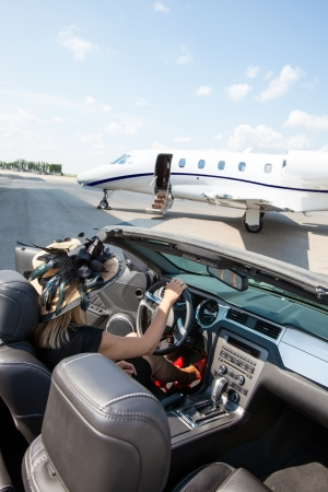Woman in convertible with private jet in background at airport terminal Stock Photo - 25296707