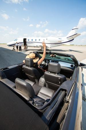 rijke vrouw: Rijke vrouw in converteerbare wuivende hand om piloot en stewardess tegen prive-jet op de luchthaven terminal