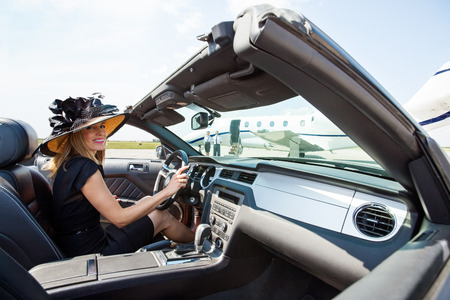 happy rich woman: Portrait of woman driving convertible towards private jet at airport terminal Stock Photo