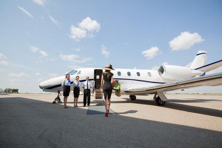 プライベート ジェットのパイロットとスチュワーデスの空港ターミナルに立って中に向かって歩いて豊かな女性の後姿 写真素材
