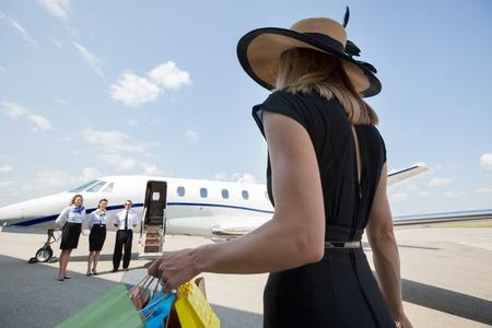 rijke vrouw: Achteraanzicht van rijke vrouw met boodschappentassen lopen naar prive-jet, terwijl piloot en stewardessen die zich bij luchthaven terminal Stockfoto