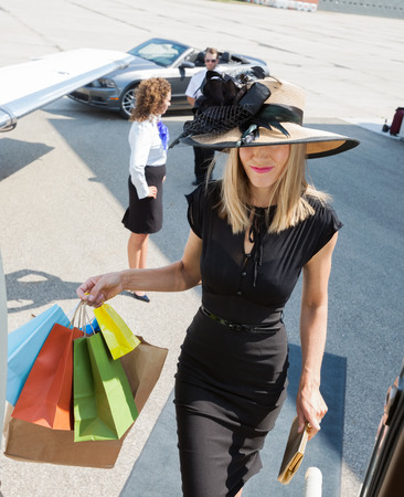 Rich woman carrying shopping bags while boarding private jet with pilot and airhostess in background at airport terminal photo