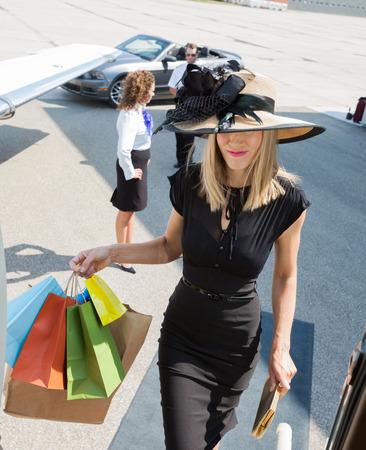 rijke vrouw: Rijke vrouw met boodschappentassen terwijl het instappen prive-jet met piloot en stewardess in de achtergrond op de luchthaven terminal Stockfoto