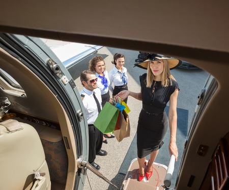 Full length portrait of rich woman with shopping bags boarding private jet while pilot and airhostess looking at her photo