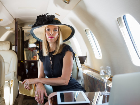 Portrait of confident rich woman sitting in private jet Stock Photo